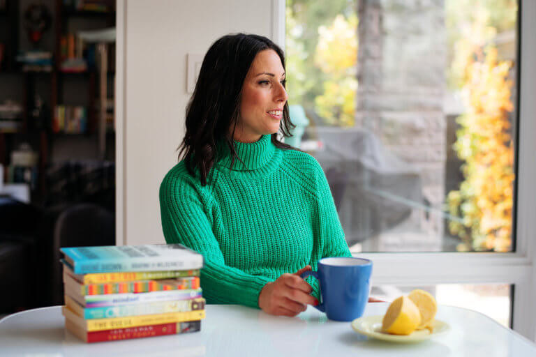 JodiLarryND.com - Dr. Jodi Larry sits at a big white table with stacked books while holding a blue teacup next to a plate of lemons