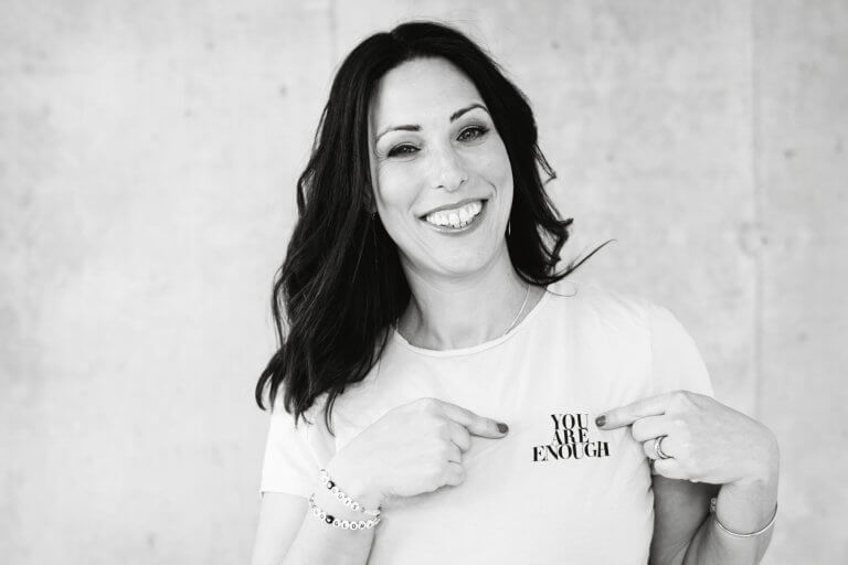 Jodi Larry black and white photo wearing a t-shirt that says I am enough.